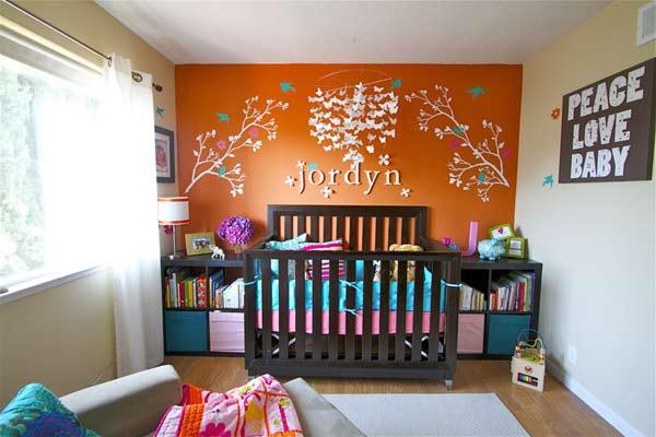 Βρεφικό δωμάτιο με έναν πορτοκαλί τοίχο.